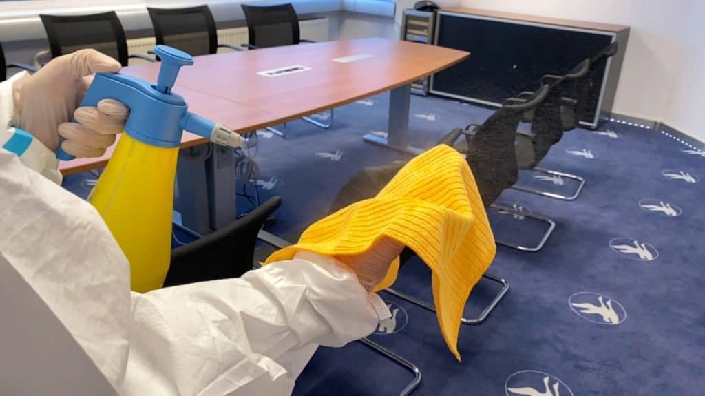 Desinfektor besprüht Lappen mit einer Flüssigkeit